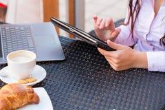Manos de la empresaria con el ordenador portátil y el teléfono móvil durante el desayuno. Fotos de archivo libres de regalías