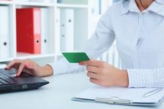 Manos de la empresaria en el traje que sostiene la tarjeta de crédito y que hace la compra en línea usando la PC del cuaderno foto de archivo