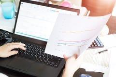 Manos de la empresaria que llevan a cabo la carta del análisis con el ordenador portátil y el Ca Imagen de archivo
