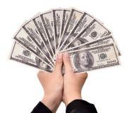 Manos de la empresaria que llevan muchos dólares del dinero Foto de archivo libre de regalías