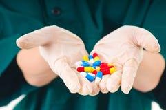 Manos de la enfermera con los guantes y las píldoras Foto de archivo libre de regalías