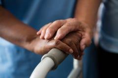 Manos de la enfermera y de la mujer mayor que detienen al caminante en clínica de reposo Imagen de archivo