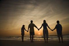 Manos de la explotación agrícola de la familia en la playa Foto de archivo libre de regalías