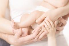Manos de la familia y pie recién nacido del bebé, padre Arms, pies recién nacidos de la madre del niño del abrazo del cuerpo de l Imágenes de archivo libres de regalías