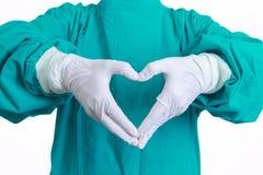 Manos de la forma del corazón del doctor del cirujano en el vestido verde en b blanco imágenes de archivo libres de regalías