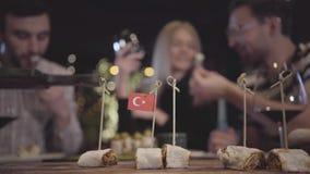 Manos de la gente borrosa que toma los pedazos de kebab rodados en la pita que miente en el tablero con la paja stucked con peque almacen de metraje de vídeo