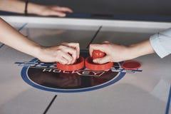 Manos de la gente joven que sostiene el huelguista en la tabla del hockey del aire en sitio de juego foto de archivo