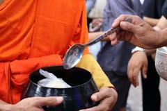 Manos de la gente mientras que comida puesta a un monk& budista x27; las limosnas de s ruedan en el extremo de Lent Day budista Foto de archivo libre de regalías