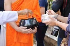 Manos de la gente mientras que comida puesta a un monk& budista x27; las limosnas de s ruedan en el extremo de Lent Day budista Fotografía de archivo libre de regalías