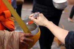 Manos de la gente mientras que comida puesta a un monk& budista x27; las limosnas de s ruedan en el extremo de Lent Day budista Imagen de archivo libre de regalías