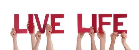 Manos de la gente que llevan a cabo la palabra recta roja Live Life Foto de archivo libre de regalías
