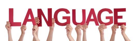 Manos de la gente que llevan a cabo lengua de palabra recta roja Imágenes de archivo libres de regalías
