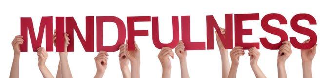 Manos de la gente que llevan a cabo Mindfulness recto rojo de la palabra Fotos de archivo