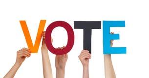 Manos de la gente que llevan a cabo voto recto colorido de la palabra Imagen de archivo libre de regalías