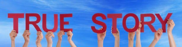 Manos de la gente que sostienen el cielo azul de la historia verdadera recta roja de la palabra imagen de archivo