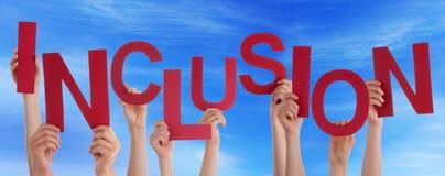 Manos de la gente que sostienen el cielo azul de la inclusión roja de la palabra Imagen de archivo libre de regalías
