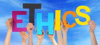 Manos de la gente que sostienen el cielo azul de los éticas coloridos de la palabra Fotografía de archivo libre de regalías