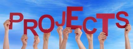 Manos de la gente que sostienen el cielo azul de los proyectos de Word rojos foto de archivo libre de regalías