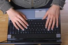 Manos de la hembra en el teclado del cuaderno Foto de archivo libre de regalías