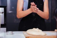 Manos de la hembra de la mujer del panadero que hace la pasta de la harina que aplaude Foto de archivo