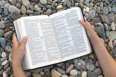 Manos de la hembra que sostienen la biblia abierta Foto de archivo libre de regalías
