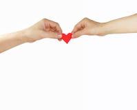 Manos de la hembra y del hombre con el corazón rojo Imagen de archivo
