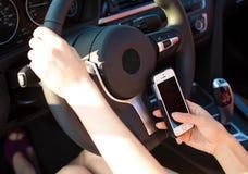 Manos de la imagen, mujer que envía el mensaje de texto en el teléfono elegante mientras que dri Foto de archivo