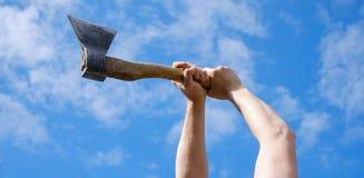 Manos de la leña choping del hombre con el hacha en el cielo azul imagen de archivo