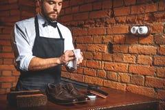 Manos de la limpieza del zapatero en su taller Fotos de archivo libres de regalías