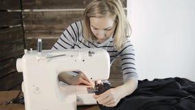 Manos de la máquina de coser y de la mujer, modista que apoya un paño metrajes