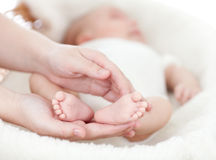 Manos de la madre que llevan a cabo los pies del pequeño bebé Fotos de archivo libres de regalías