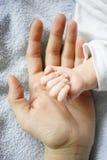 Manos de la madre y del bebé Fotos de archivo