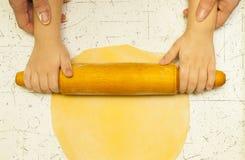 Manos de la madre y del hijo que amasan la pasta en la tabla Imagen de archivo libre de regalías