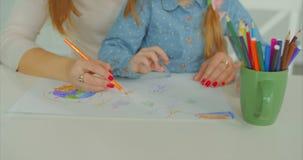 Manos de la madre y del niño que crean las ilustraciones en el escritorio almacen de metraje de vídeo