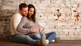 Manos de la mamá y del papá en la panza embarazada que muestra la muestra del corazón Pares embarazadas que acarician el vientre  metrajes