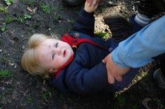 Manos de la mama que ayudan al bebé para arriba Imagen de archivo libre de regalías