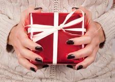 Manos de la muchacha con la caja de regalo roja negra de los controles del clavo y del suéter Imágenes de archivo libres de regalías