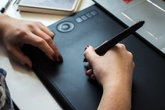 Manos de la muchacha en una tableta gráfica Imagenes de archivo