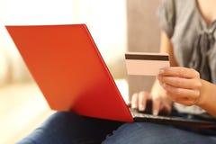 Manos de la muchacha que compran la tarjeta de crédito que se sostiene en línea Fotos de archivo libres de regalías