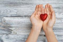 Manos de la muchacha que llevan a cabo un corazón rojo chispeante Visión superior Día del `s de la tarjeta del día de San Valentí Fotografía de archivo
