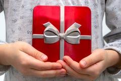 Manos de la muchacha que muestran el regalo en una caja, sosteniendo la caja de regalo roja con el arco sobre fondo del día de fi imágenes de archivo libres de regalías