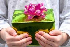 Manos de la muchacha que muestran el regalo en una caja, sosteniendo la caja de regalo verde con el arco sobre fondo del día de f foto de archivo libre de regalías