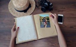 Manos de la muchacha que sostiene un álbum para las fotos con una cámara, un p foto de archivo