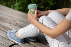 Manos de la muchacha que sostienen una taza de café en las piernas en pantalones rayados y que se sientan en un banco en el parqu foto de archivo libre de regalías