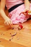 Manos de la muchacha que toman pedazos de la bola de la Navidad Imagenes de archivo