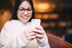 Manos de la muchacha usando un teléfono elegante Foto de archivo libre de regalías