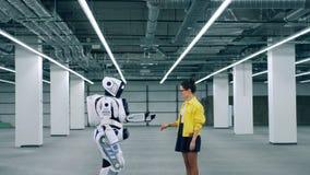 Manos de la muchacha y del tacto del droid mientras que se encuentra en un cuarto almacen de metraje de vídeo