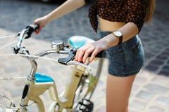 Manos de la muchacha y manillar de la bicicleta Foto de archivo