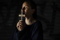 Manos de la mujer adulta que llevan a cabo la cruz que ruega para la religión de dios Fotografía de archivo