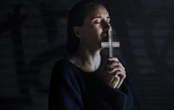 Manos de la mujer adulta que llevan a cabo la cruz que ruega para la religión de dios Imagenes de archivo
